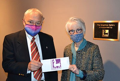 James Draper, President of the Founders Society, presents Kathryn Sharbaugh, Director of Donor Relations & Special Projects, with a check in support of the Graphic Gallery