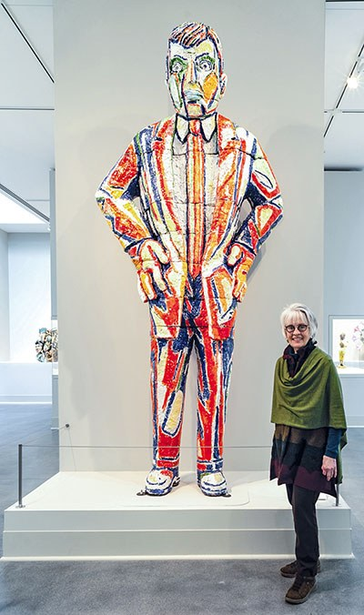 Kathryn Sharbaugh standing with Frey Sculpture of Arrogant Man